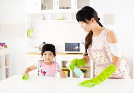 niña ayudando a su madre mesa limpia en la cocina Foto de archivo