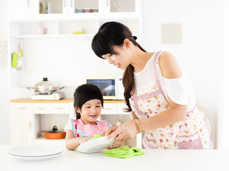 little girl helping her mother clean dish in the kitchen