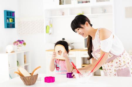 少女の母親が台所で調理を支援 写真素材 - 66062512