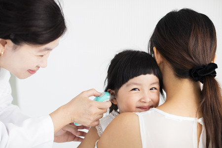 vrouwelijke arts die de temperatuur met behulp van in oorthermometer Stockfoto