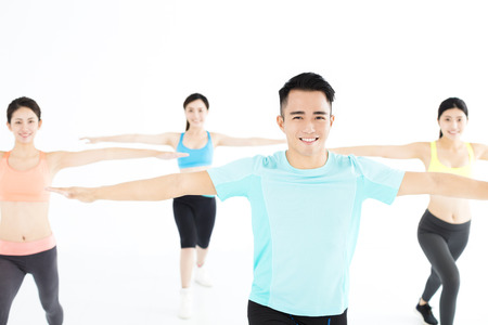 smiling young fit group stretching in gym photo