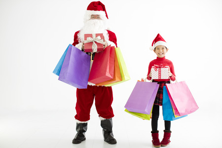 happy little girl and santa claus holding shopping bags photo