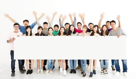 행복 한 젊은 그룹 빈 보드를 게재