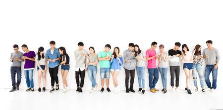 幸せな若い学生グループ見てスマート フォン
