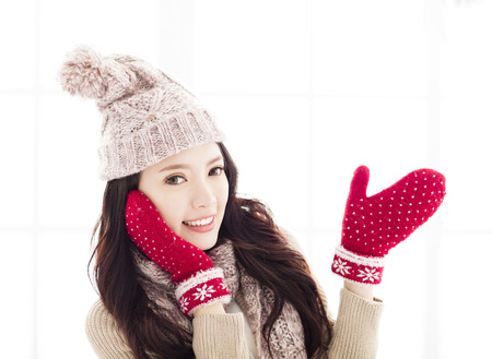 young woman in winter clothing showing open hand Stock Photo