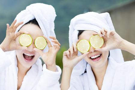 tratamientos corporales: hermosa mujer mostrando limón fresco en el spa Foto de archivo