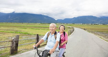 happy Senior  Couple Riding Bicycle on country road photo