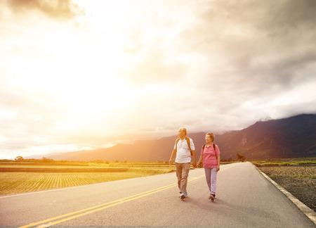 äldre par vandring på landsvägen