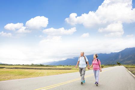 pareja de alto nivel de excursión en el camino rural Foto de archivo