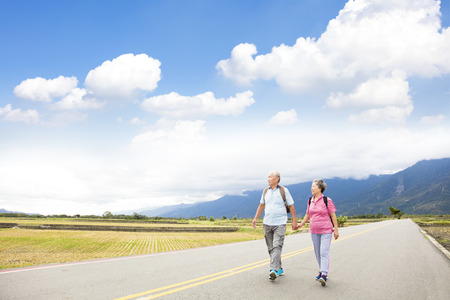 2 way: senior couple hiking on the country road Stock Photo