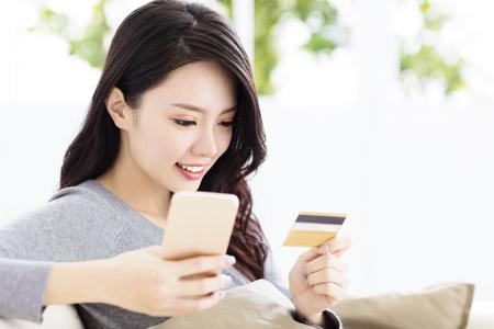신용 카드와 스마트 폰을 가진 젊은 아름 다운 여자
