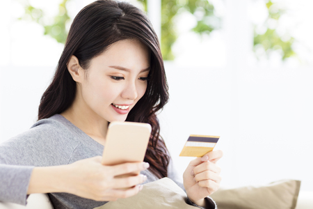 young beautiful woman with credit card and smart phone