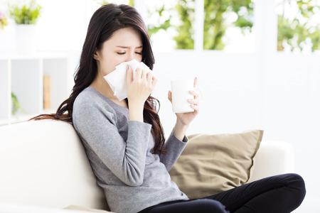 estornudo: Mujer joven infecta con el frío que sopla su nariz