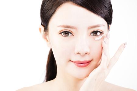 Jonge vrouw die huidcrème onder ogen toepast
