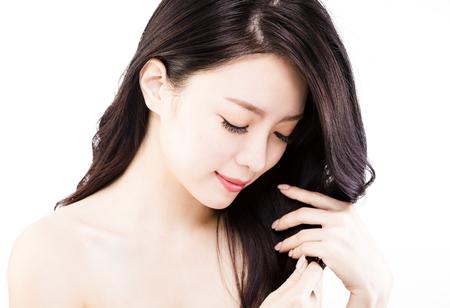 młoda kobieta dotykania jej zdrowe czarne włosy