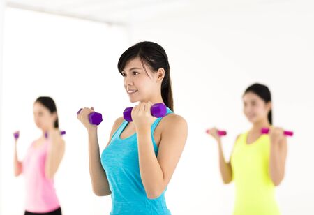asia women: young woman doing exercise with dumbbell in gym Stock Photo