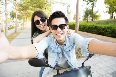 road of love: happy young couple riding  scooter and making selfie photo Stock Photo
