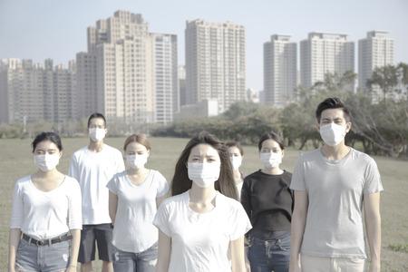 junge Gruppe tragen Mundschutz gegen die Luftverschmutzung in der Stadt