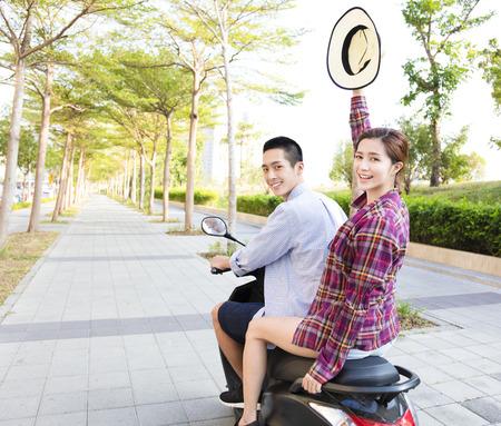 町で幸せな若いカップル乗りスクーター