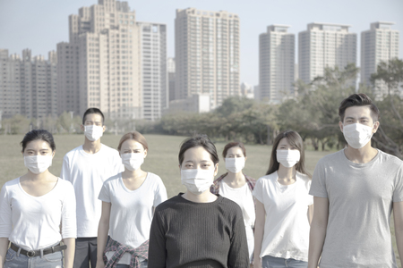 young group wearing mouth mask against air pollution in city photo