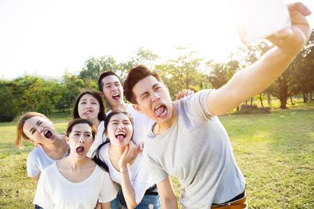 grupo de jóvenes felices teniendo autofoto en el parque