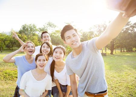 jeune heureux groupe prenant selfie dans le parc Banque d'images