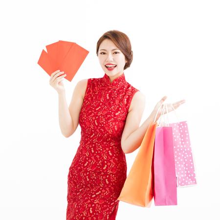 donna cinese in possesso di borse per la spesa e buste rosse