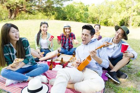 Glückliche junge Gruppe genießen Picknick-Partei Standard-Bild - 71326947
