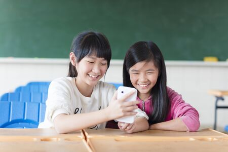 lady on phone: Two teenage girls student watching the phone in classroom