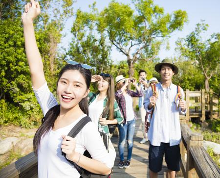 gelukkige jonge groep wandelen samen door het bos