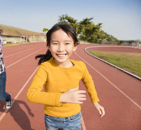 asian children: happy little girls running on the track