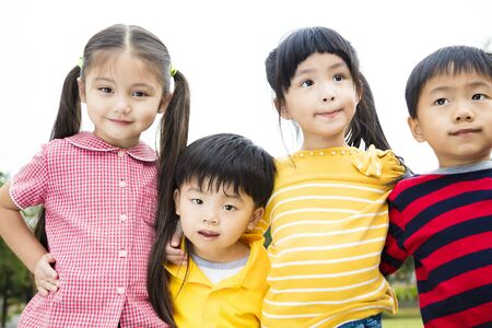 Group of smiling kids standing outside together photo