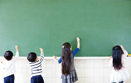 rear view of school students drawing on chalkboard photo