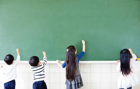 rear view: rear view of school students drawing on chalkboard