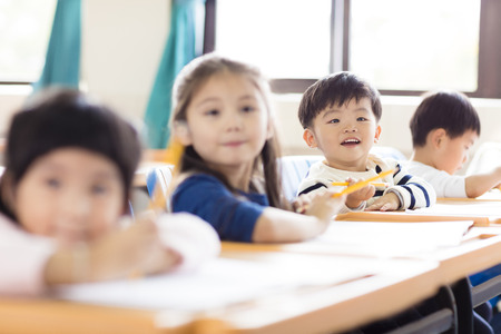 asian group: happy little boy studying  in the classroom