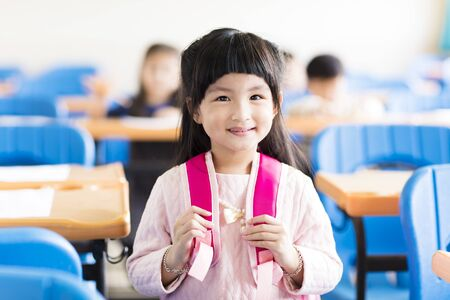 book: happy little girl student  in the classroom