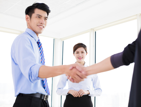 happy asian people: happy businessmen making agreement and colleague standing near by