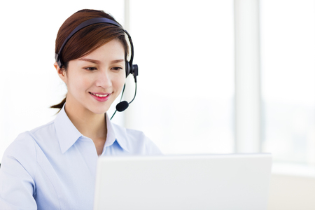 help: young business Woman wearing headset in office Stock Photo