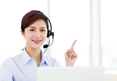 オフィスで若いビジネス女性の身に着けているヘッドセット 写真素材