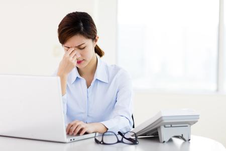 Jonge zakenvrouw met moe ogen en hoofdpijn