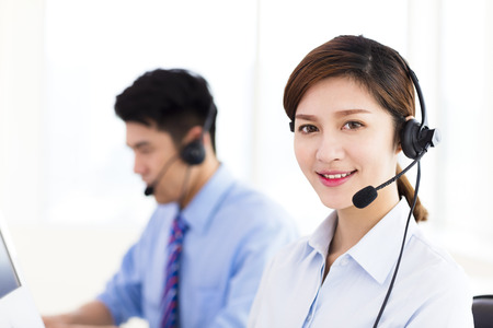 lady on phone: business Woman and man wearing headset in office Stock Photo