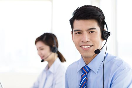 office desk: business Woman and man wearing headset in office Stock Photo