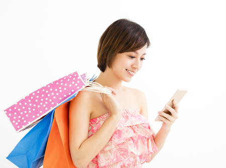 customer: woman with shopping bags and watching smart phone