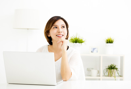 young woman with laptop and thinking in living room