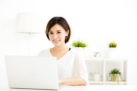 study: happy young woman with laptop in living room Stock Photo