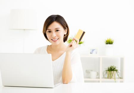 Jonge vrouw online winkelen en met creditcard betalen Stockfoto
