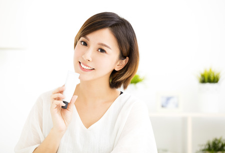 smiling young woman showing skincare products Stok Fotoğraf - 73565009