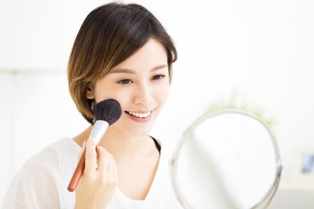 젊은 여자가 거울 앞에 화장을하고 스톡 콘텐츠