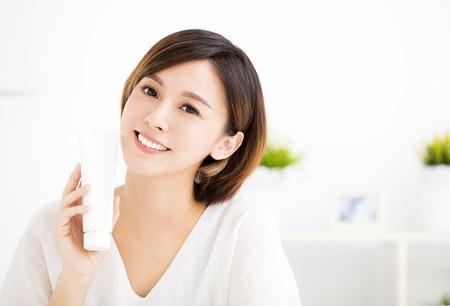lachende jonge vrouw toont huidverzorgingsproducten