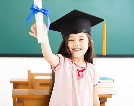Retrato de colegiala linda con sombrero de graduación en el aula Foto de archivo